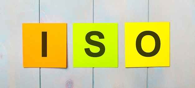 Drie gekleurde stickers met de tekst iso op een lichtblauwe houten ondergrond