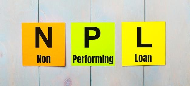 Drie gekleurde stickers met de tekst npl non performing loan op een lichtblauwe houten ondergrond
