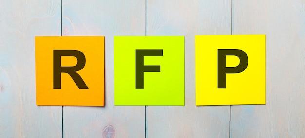 Drie gekleurde stickers met de tekst rfp op een lichtblauwe houten ondergrond