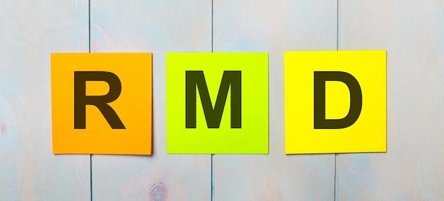 Drie gekleurde stickers met de tekst rmd required minimum distributions op een lichtblauwe houten achtergrond