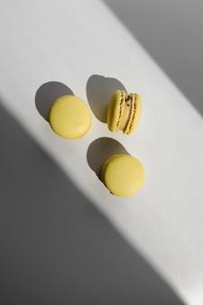 Drie gele citroen franse bitterkoekjes of macarons dessert op witte achtergrond met lichtstralen uit raam.