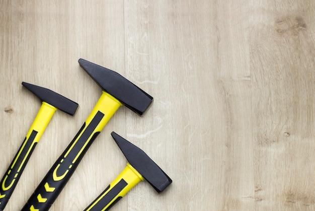 Drie gele moderne hamers met glasvezelhandvat op houten achtergrond. bovenaanzicht van bovenaf.