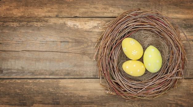 Drie gele paaseieren in vogelnest op houten achtergrond - bovenaanzicht