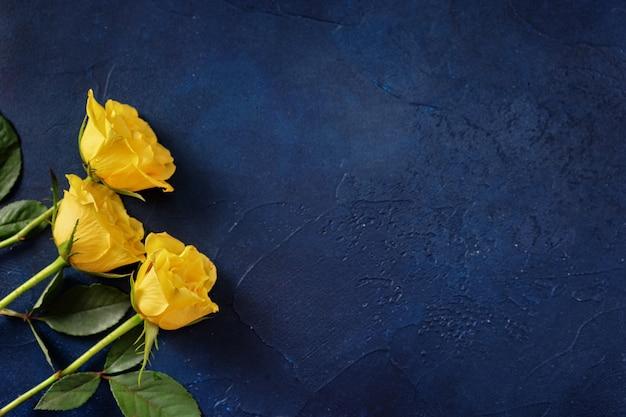 Drie gele rozen op donkerblauwe achtergrond met een ruimte voor een tekst