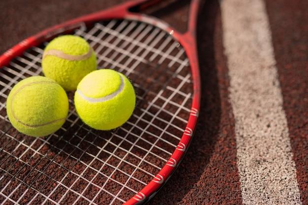 Drie gele tennisbollen die op racket door witte lijn op stadionspeelplaats liggen