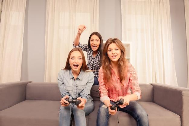 Drie gelukkige aantrekkelijke meisjes die thuis videospelletjes spelen