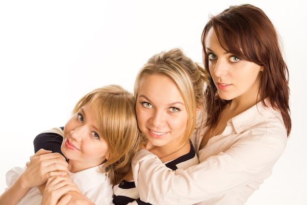 Drie gelukkige aantrekkelijke tienermeisjesvrienden die rijtjes in een rij hoofd en schouderportret op wit stellen