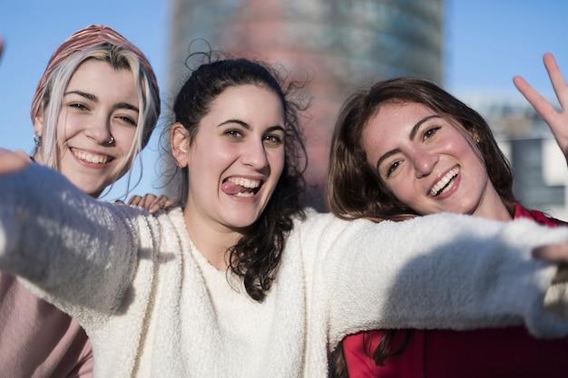 Drie gelukkige beste vriendinnen buitenshuis maken selfie op smartphone.