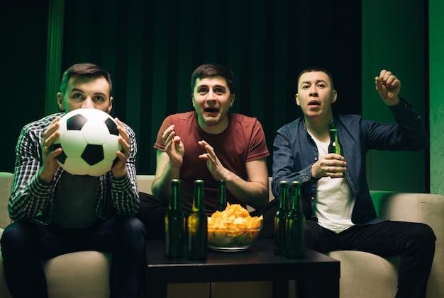 Drie gelukkige blanke vriendelijke mannen chips snacks eten en juichen voor voetbalwedstrijd