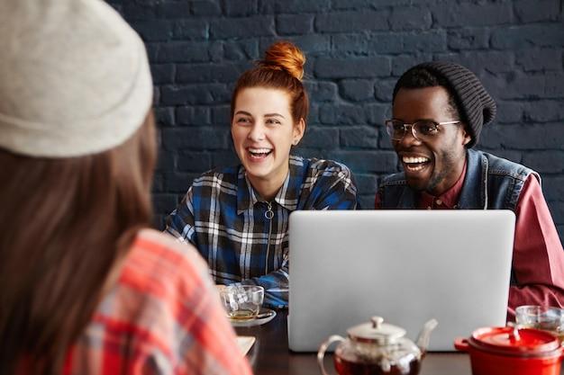 Drie gelukkige enthousiaste jonge mensen met behulp van laptopcomputer, chatten aan tafel in café. internationaal team bespreken zakelijke ideeën tijdens de lunch.