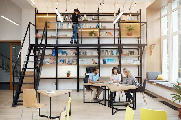 Drie gelukkige enthousiaste ontwerpers bespreken zakelijke ideeën voor aanstaande project zittend aan tafel met papieren in heldere moderne bibliotheek. comfortabel samenwerken met vrienden. opstarten, bedrijfsconcept