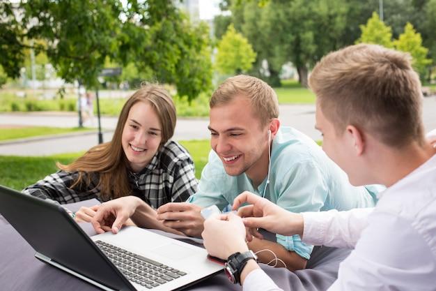 Drie gelukkige glimlachende jonge vrienden die laptop in in openlucht het plaatsen bekijken.