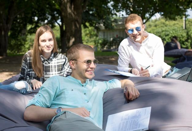 Drie gelukkige glimlachende studenten die in openlucht op een groot kussen ontspannen en hun huiswerk doen.