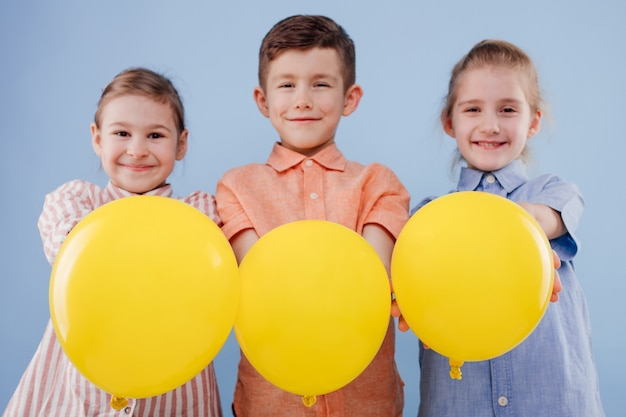Drie gelukkige jonge geitjes meisje en jongen met gele ballon met glimlach kijken naar de camera geïsoleerd op blauwe bac...