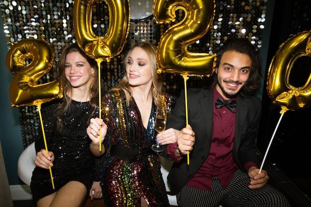 Drie gelukkige jonge vrienden die gouden opblaasbare nummers van het volgende jaar vasthouden terwijl ze plezier hebben op een feestje