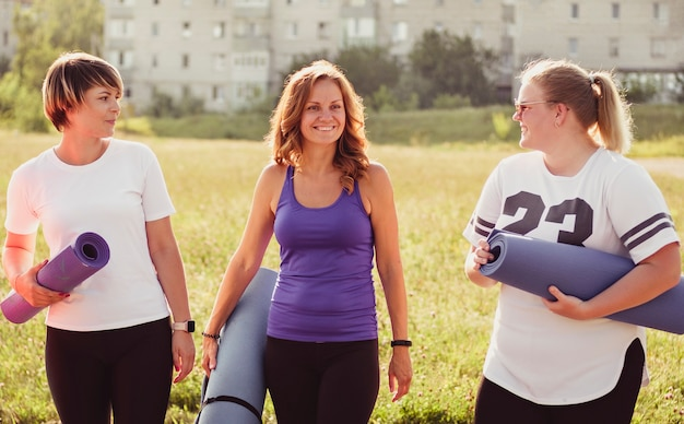 Drie gelukkige jonge vrouwen die yogamatten dragen