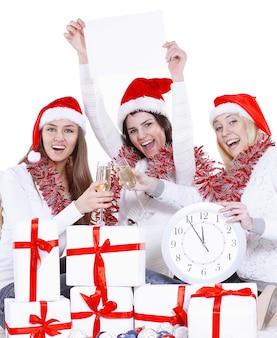Drie gelukkige jonge vrouwen in hoeden van de kerstman met klok en lege affiche die met kerstmis gelukwensen