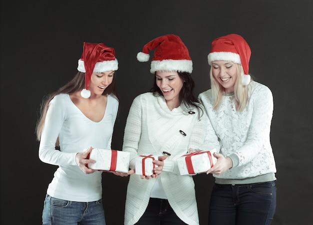 Drie gelukkige jonge vrouwen in kostuum van de kerstman met christma