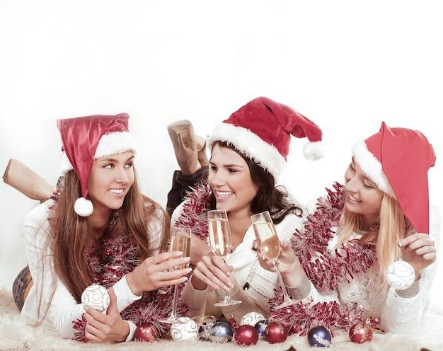 Drie gelukkige jonge vrouwen in kostuums van de kerstman