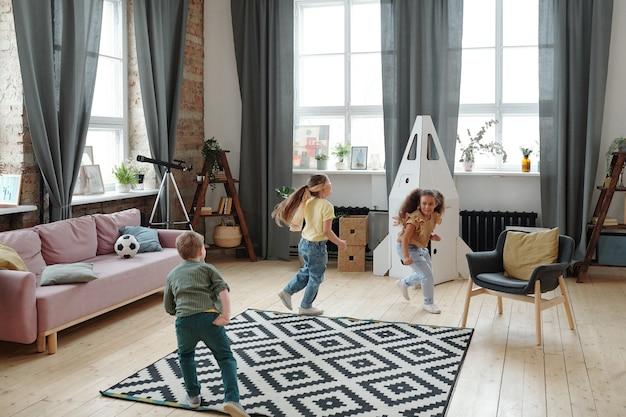 Drie gelukkige kinderen die bijpraten in de woonkamer