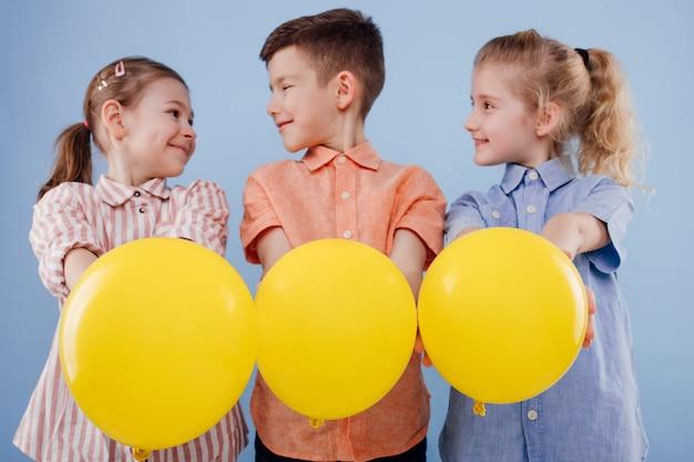 Drie gelukkige kinderen meisjes en een jongen met gele ballonnen met een glimlach geïsoleerd op blauwe achtergrond c...