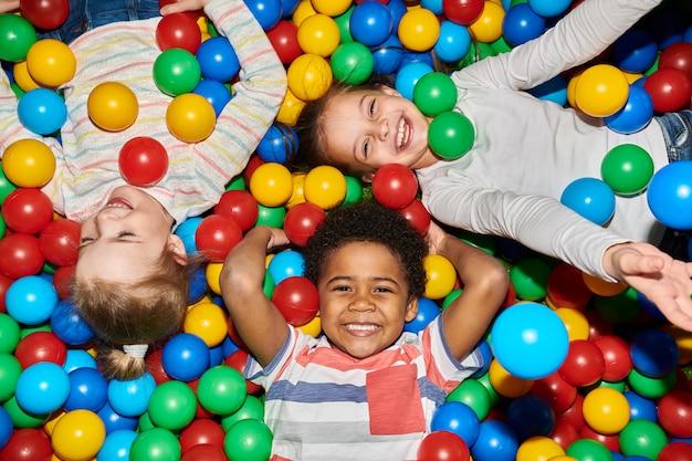 Drie gelukkige kinderen spelen in ballpit