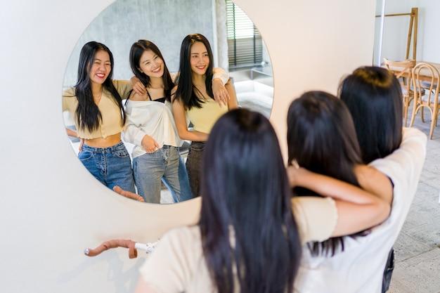 Drie gelukkige lachende jonge vrienden poseren samen voor een ronde spiegel in een kamer