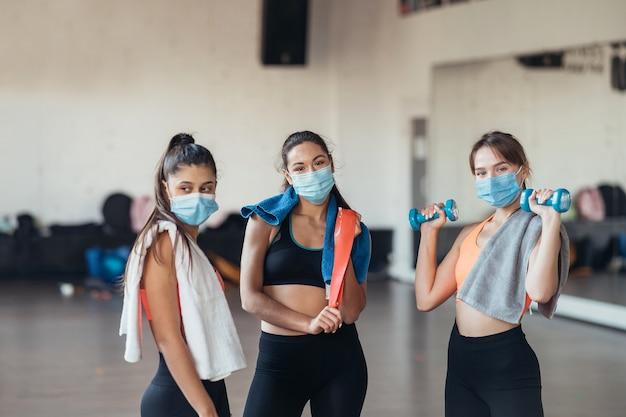 Drie gelukkige lachende positieve meisjes na de training in de sportschool. er zijn camera kijken. horizontaal.