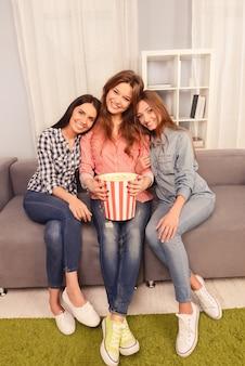Drie gelukkige meisjes die partij hebben en film met popcorn kijken