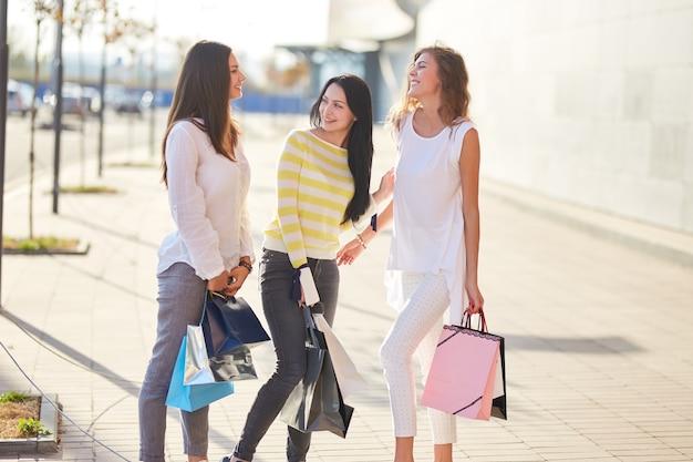 Drie gelukkige meisjes gekleed in stijlvolle vrijetijdskleding lopen met boodschappentassen