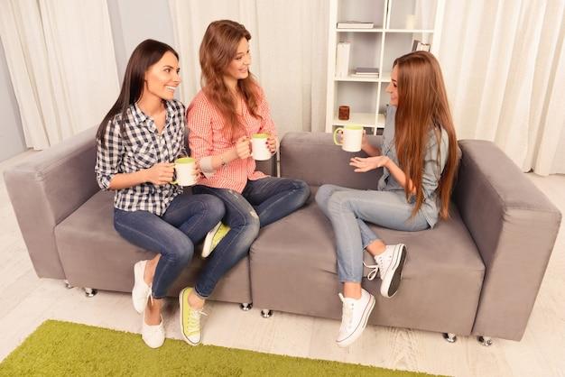 Drie gelukkige mooie meisjes die op bank zitten en met thee praten
