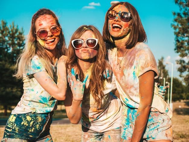 Drie gelukkige mooie meisjes die partij maken bij holi-kleurenfestival