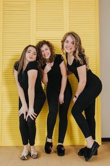 Drie gelukkige mooie meisjes in het zwarte stellen