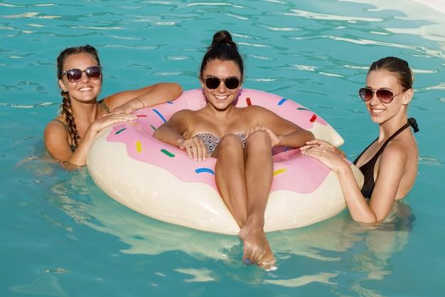 Drie gelukkige mooie vrouwelijke vrienden die een poolpartij hebben