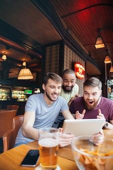 Drie gelukkige opgewonden jonge mannen kijken naar wedstrijd op tablet zittend in bar