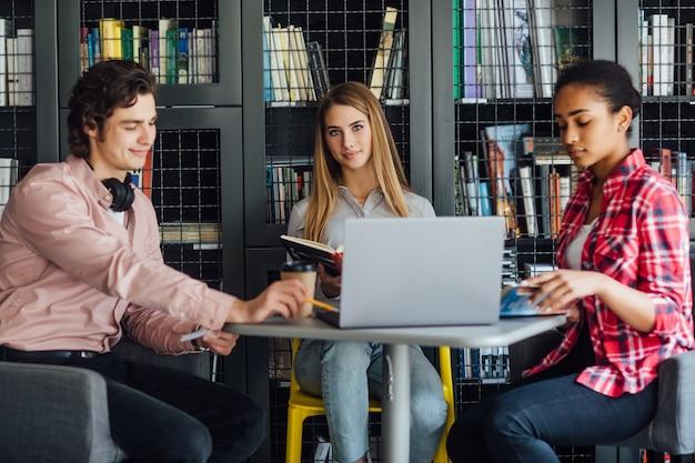 Drie gelukkige studenten schrijven naar notebooks en laptop in bibliotheek