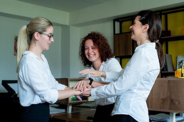 Drie gelukkige tevreden vrouwen kantoormedewerkers lachend vrolijk gestapeld hun handen gebaar van vriendschap, eenheid en partnerschap in het bedrijfsleven staan in kantoor