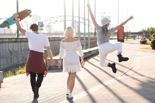 Drie gelukkige tienervrienden wandelen in een stad