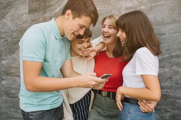 Drie gelukkige vrienden die harde het letten op video's op de school lachen.