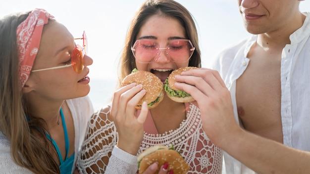 Drie gelukkige vrienden die samen hamburgers buiten eten