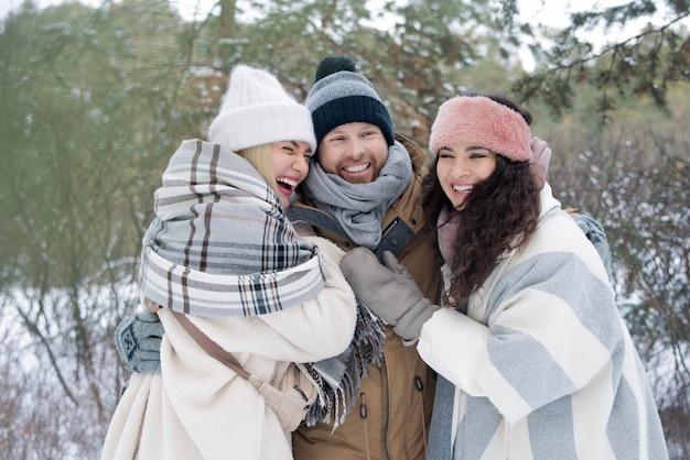 Drie gelukkige vrienden knuffelen