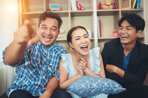 Drie gelukkige vrienden praten en grote lachen na het kijken naar grap verhaal