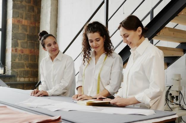 Drie gelukkige vrouwelijke modeontwerpers permanent door grote tafel in werkplaats, brainstormen en ideeën voor nieuwe collectie bespreken