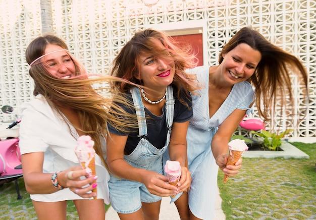Drie gelukkige vrouwelijke vrienden die roomijs hebben
