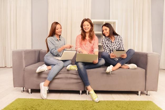 Drie gelukkige vrouwen met digitale apparaten die op internet chatten