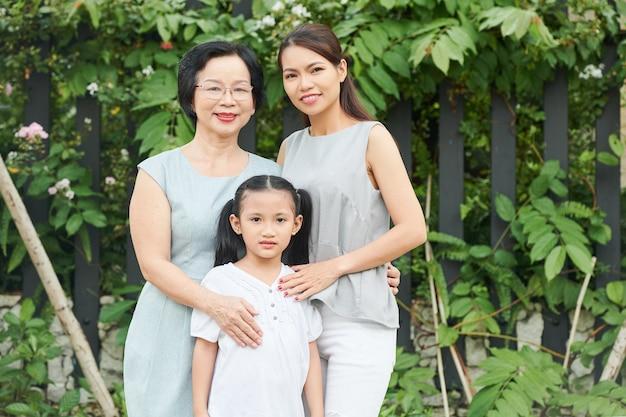 Drie generaties van één familie: grootmoeder, moeder en dochter die buiten staan