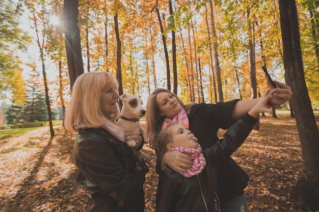 Drie generaties vrouwen en honden vinden het leuk om samen naar de camera te kijken die poseert voor een zelfportretfoto