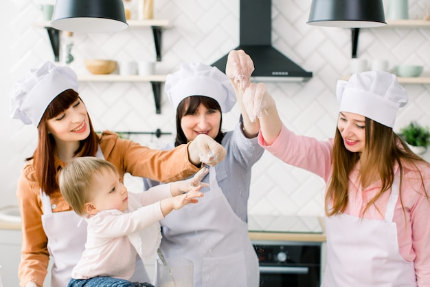 Drie generaties vrouwen in witte schorten maken tot moederdag pizzadeeg in de keuken