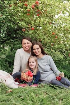 Drie generaties vrouwen van dezelfde familie in een appelboomgaard tijdens een picknick