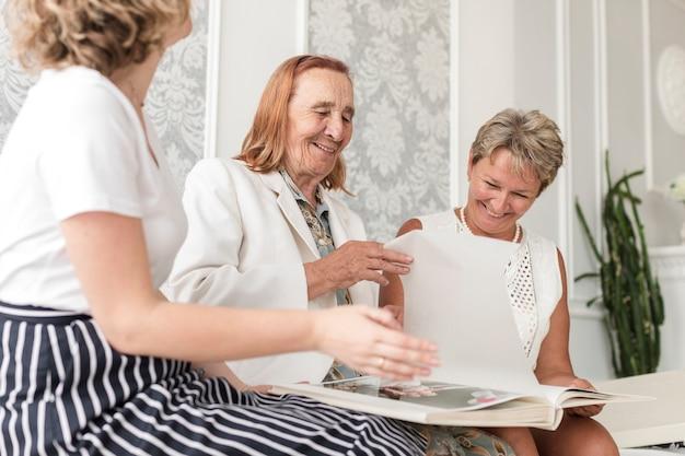 Drie generatievrouwen die samen zitten en fotoalbum thuis kijken